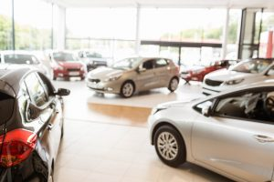 View of new and used cars inside dealership.