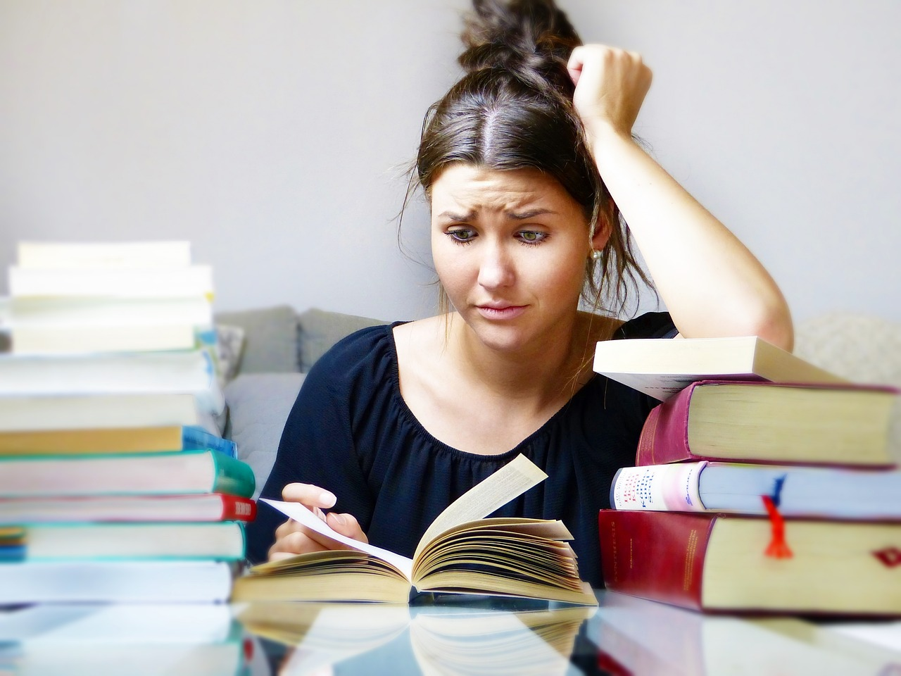 A girl reading a lot of books, looking stressed.