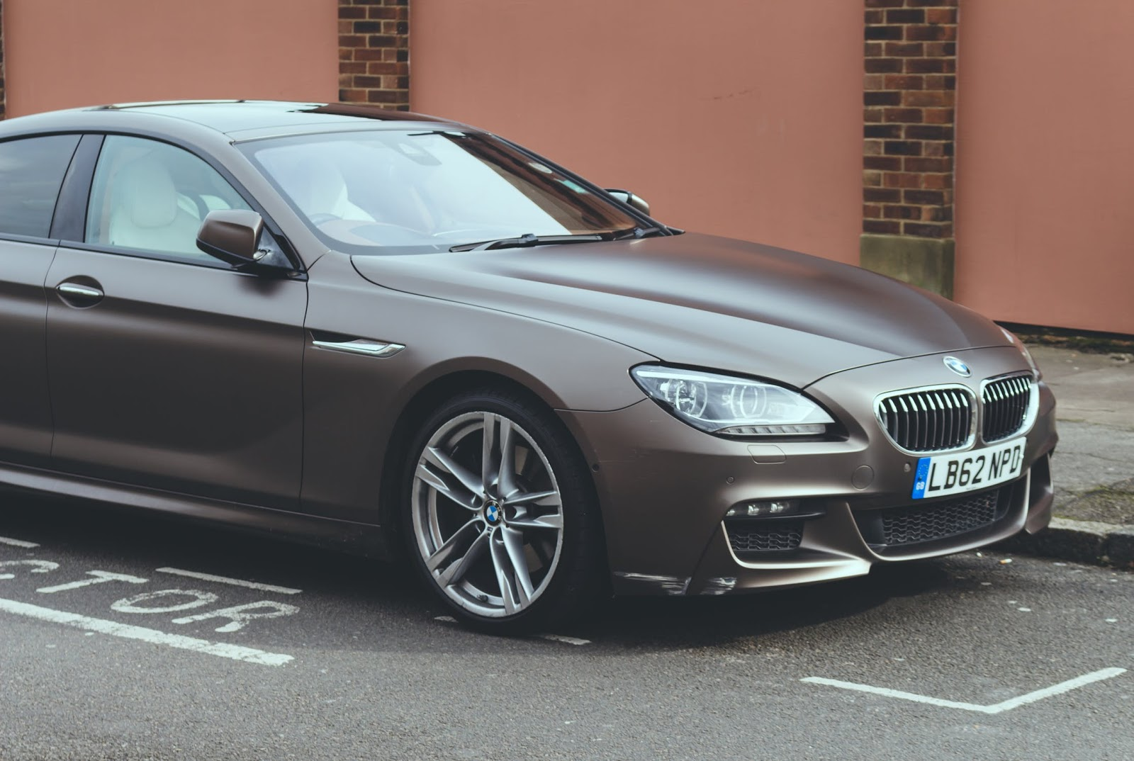 A brown BMW parked by the curb.